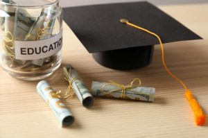 Dollar and graduation cap in the table